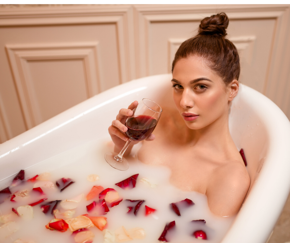 fun things to do at home: Woman having a bubble bath with roses while drinking wine